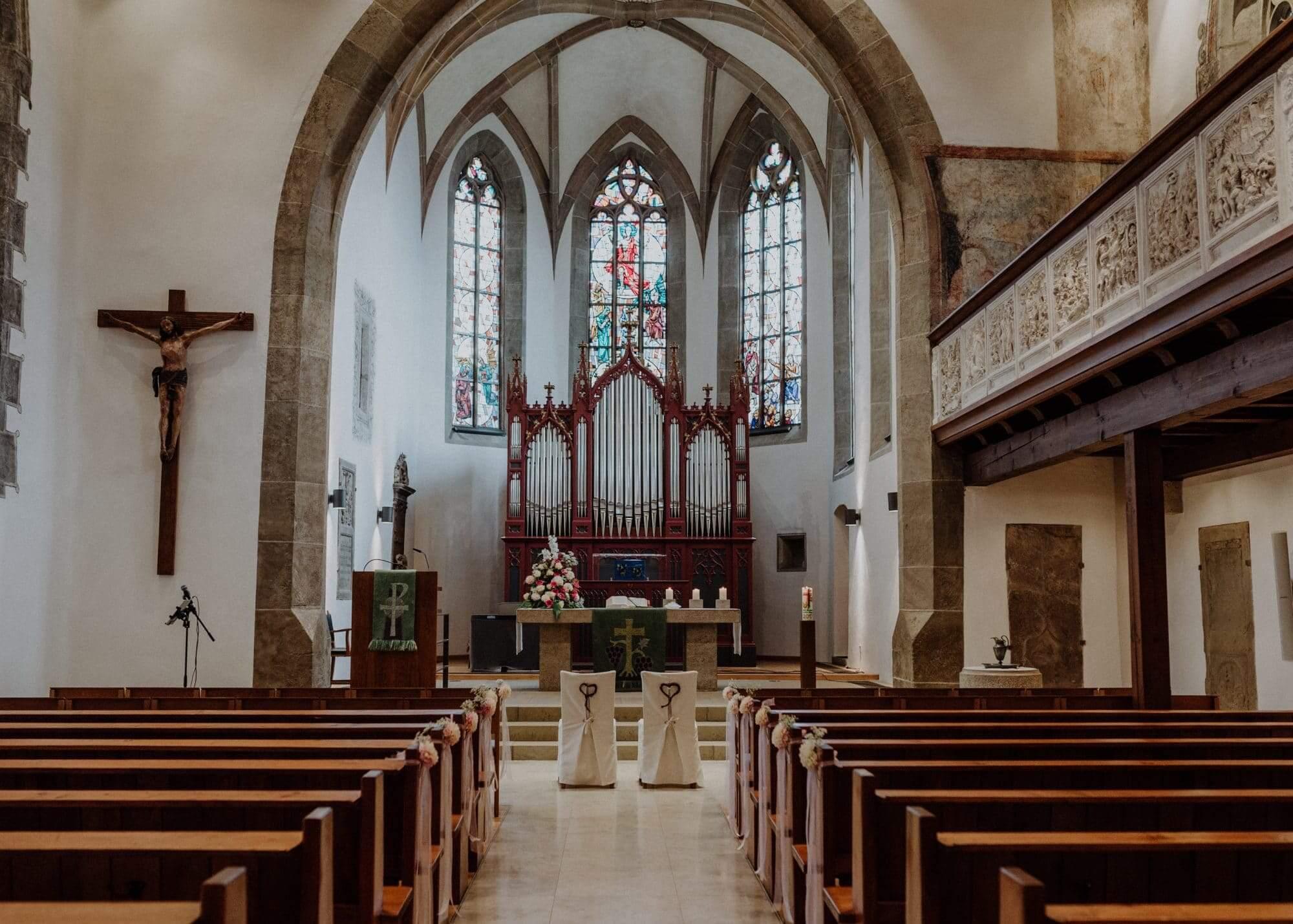 Kirche mit geschmueckten Stuehlen fuer das Brautpaar