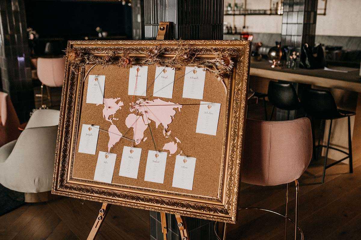 Weltkarte als Sitzplan in goldenem Rahmen auf Staffelei