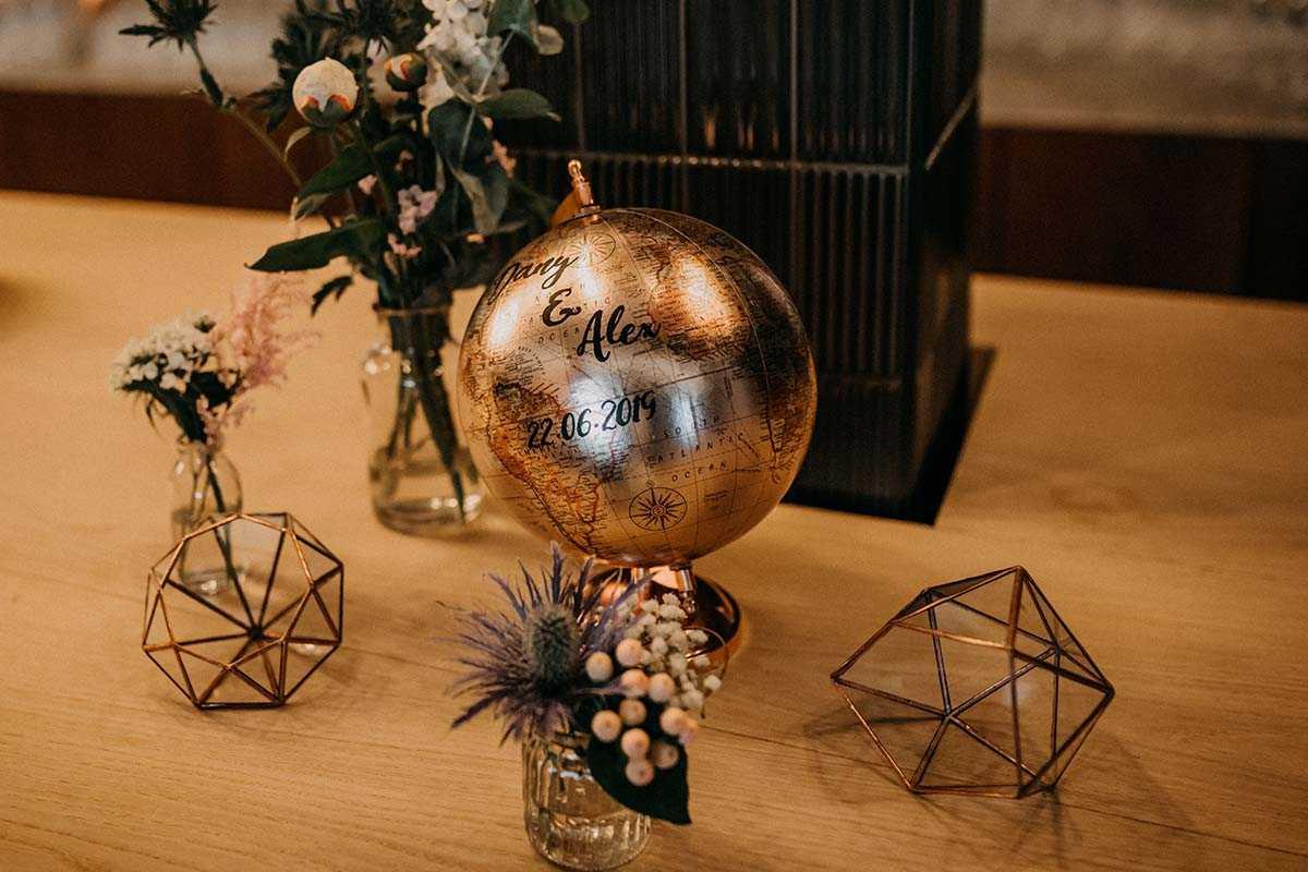Goldener Globus mit Aufschrift und Blumen
