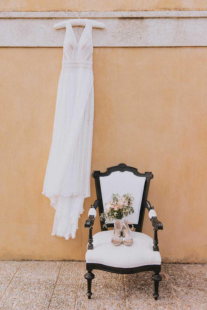 Brautkleid am Buegel und Stuhl mit Brautschuhen und Brautstrauss