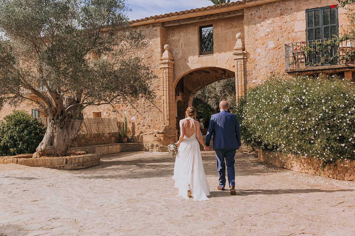 Braut und Braeutigam Hand in Hand vor der Finca