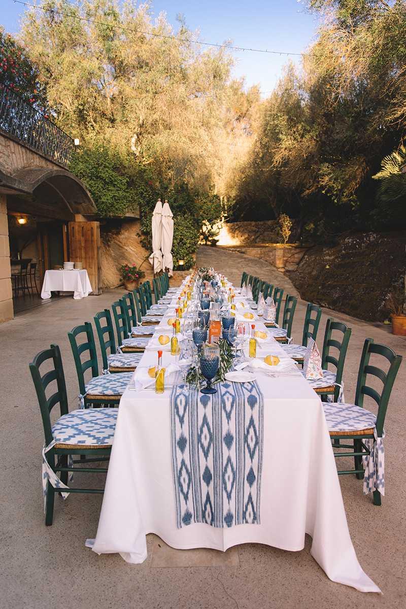 Gedeckter Tisch mit Stuehlen vor einer Finca