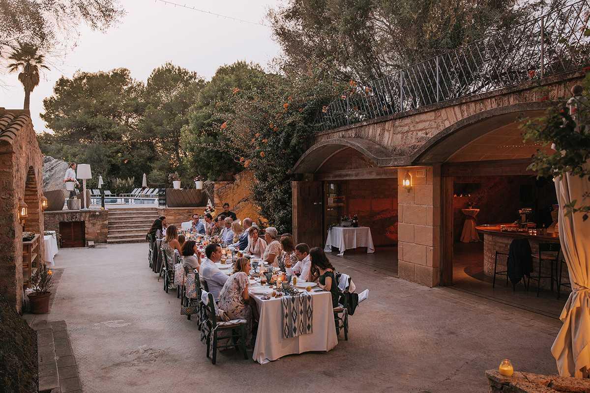 Hochzeitsgaeste an einem langen Tisch vor einer Finca