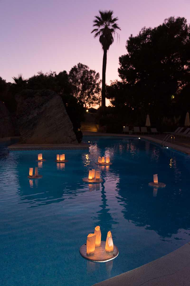 Hochzeitslocation mit beleuchtetem Pool und Palmen am Abend