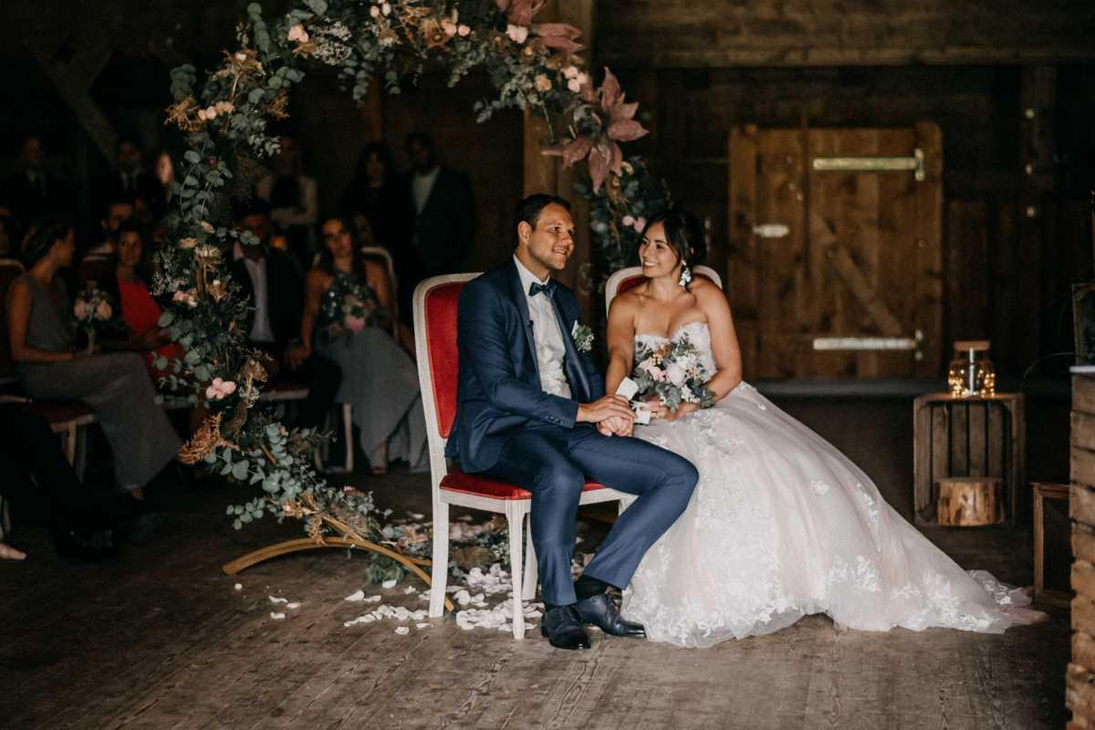 Brautpaar bei der freien Trauung in einer Scheune vor dem Traubogen aus Blumen
