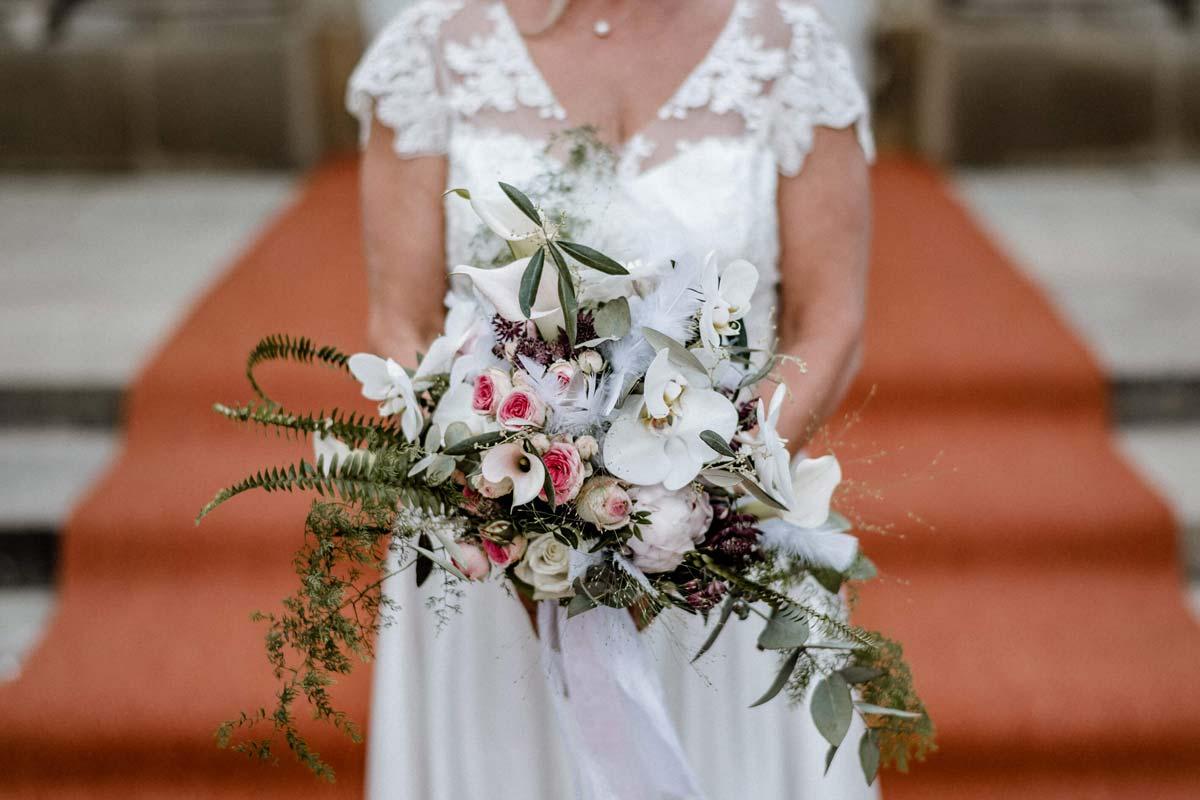Braut vor Treppen mit Brautstrauss