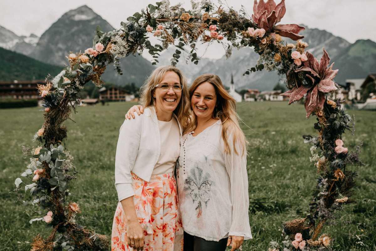 Viola Dreyer und Jana Weidmann Agentur Traumhochzeit mit dem Traubogen aus Blumen vor Bergkulisse am Achensee in Oesterreich
