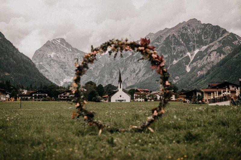 Traubogen aus Blumen vor Bergkulisse am Achensee in Oesterreich
