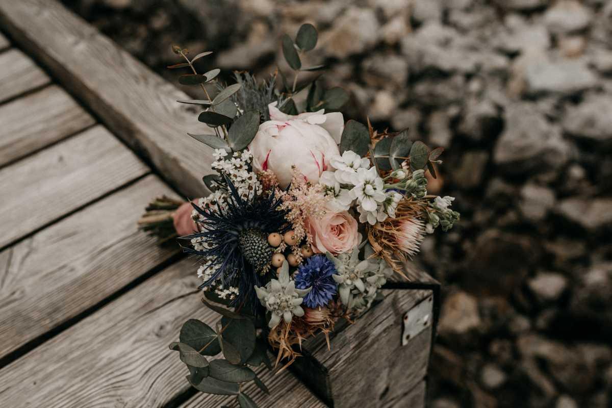 Brautstrauss mit Eukalyptus Pfingstrosen und blauen Disteln
