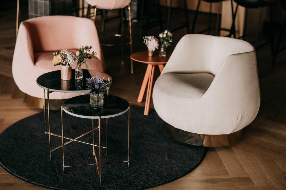 Gemuetliche Sitzgruppe aus Sesseln und Tischen mit Blumendeko