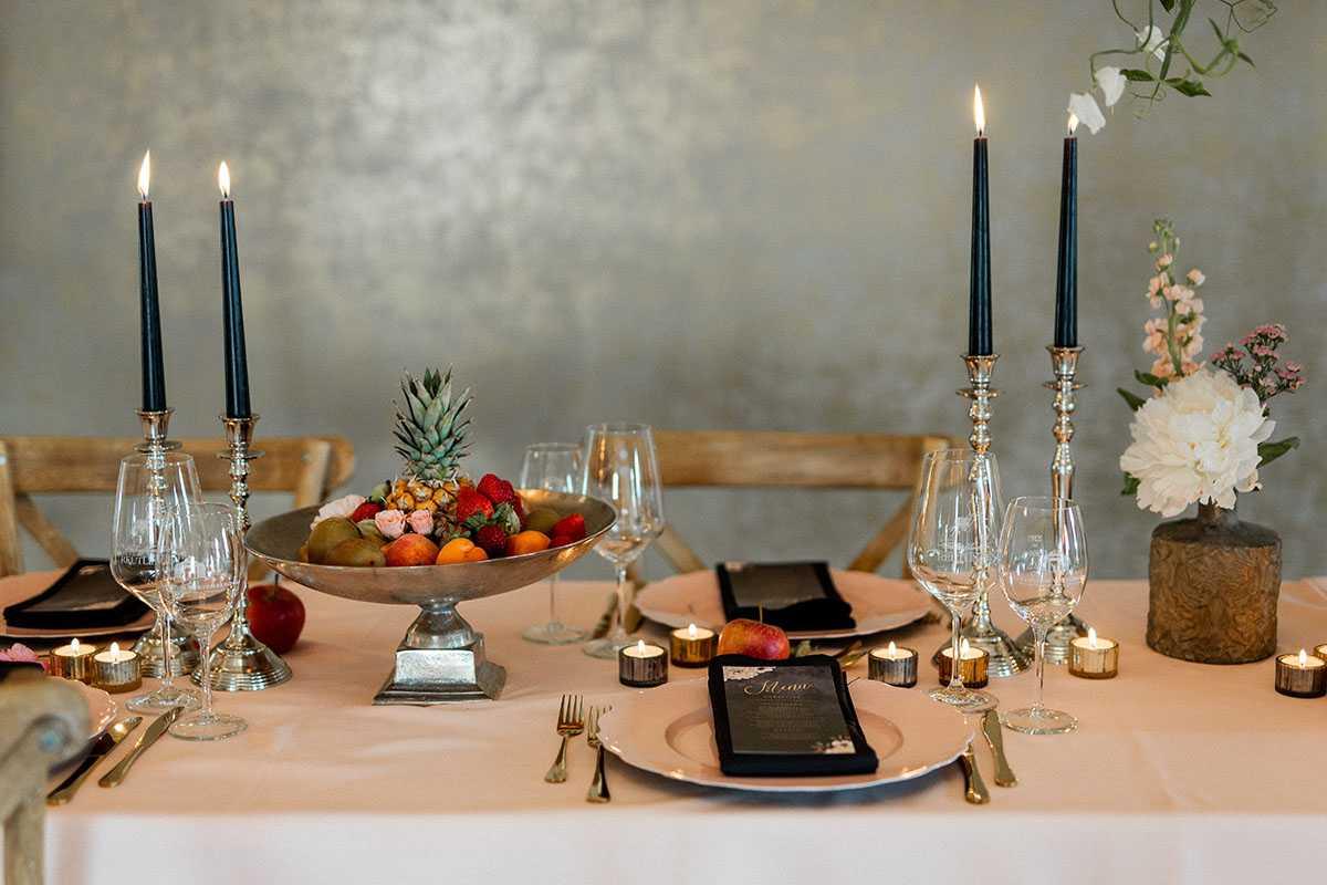 Tischdekoration mit Kerzen Blumen und Obstschale mit Fruechten