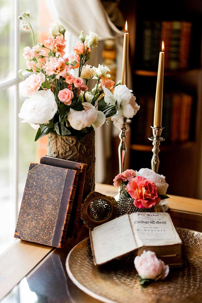 Blumenarrangement mit alten Büchern und Kerzen