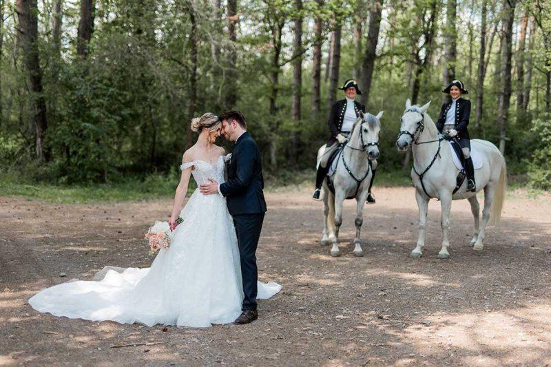 Brautpaar im Wald mit Pferden und Reitern im Hintergrund