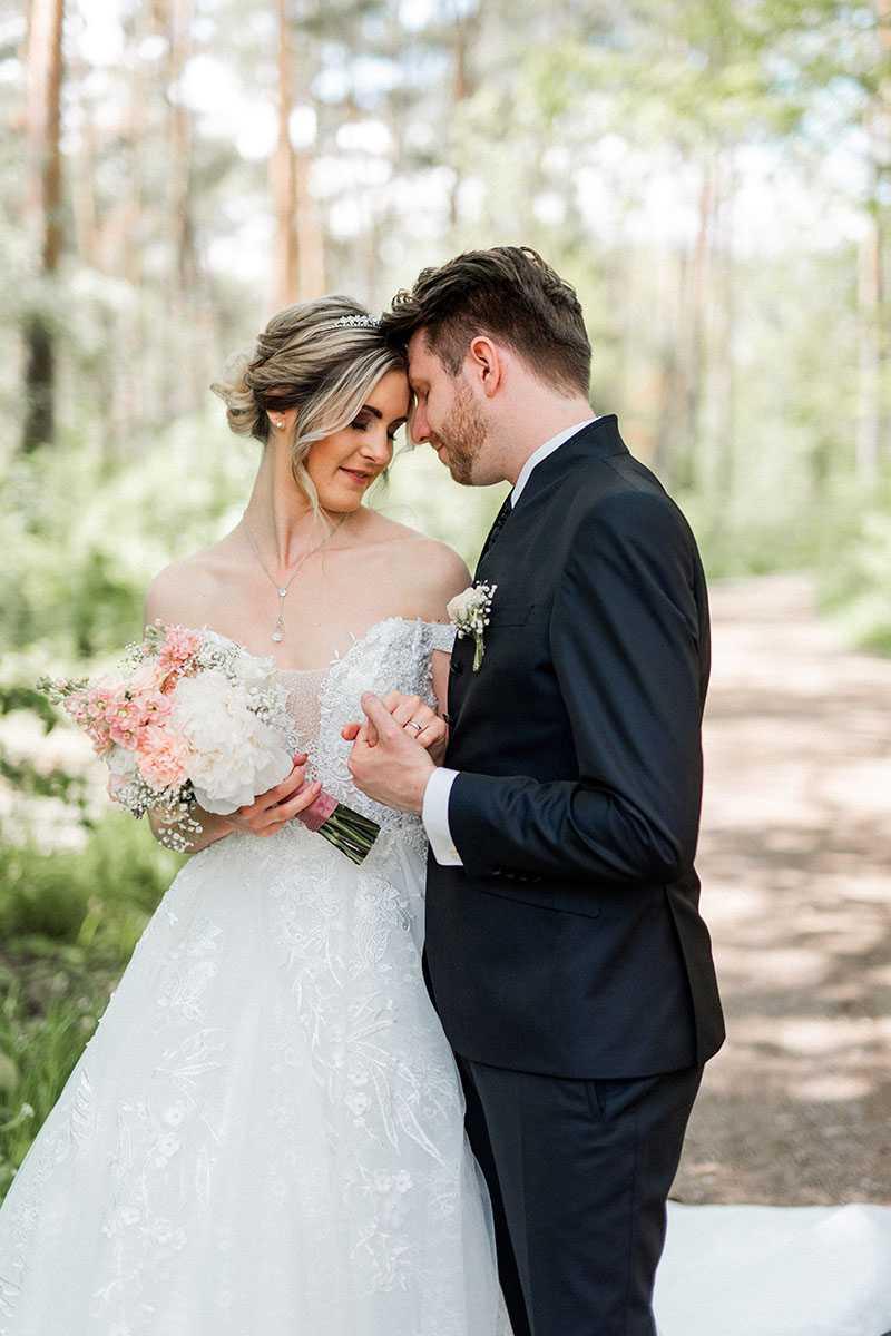Brautpaar haendchenhaltend im Wald mit Brautstrauss