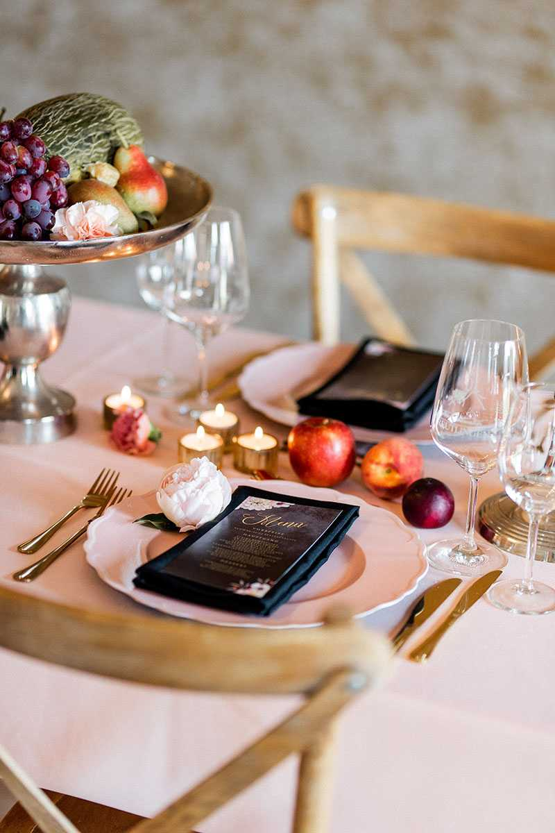 Tischdekoration mit Kerzen und Obstschale mit Fruechten