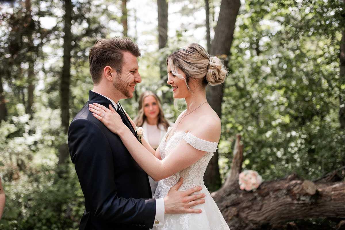 Braut und Braeutigam mit Traurednerin bei der freien Trauung im Wald