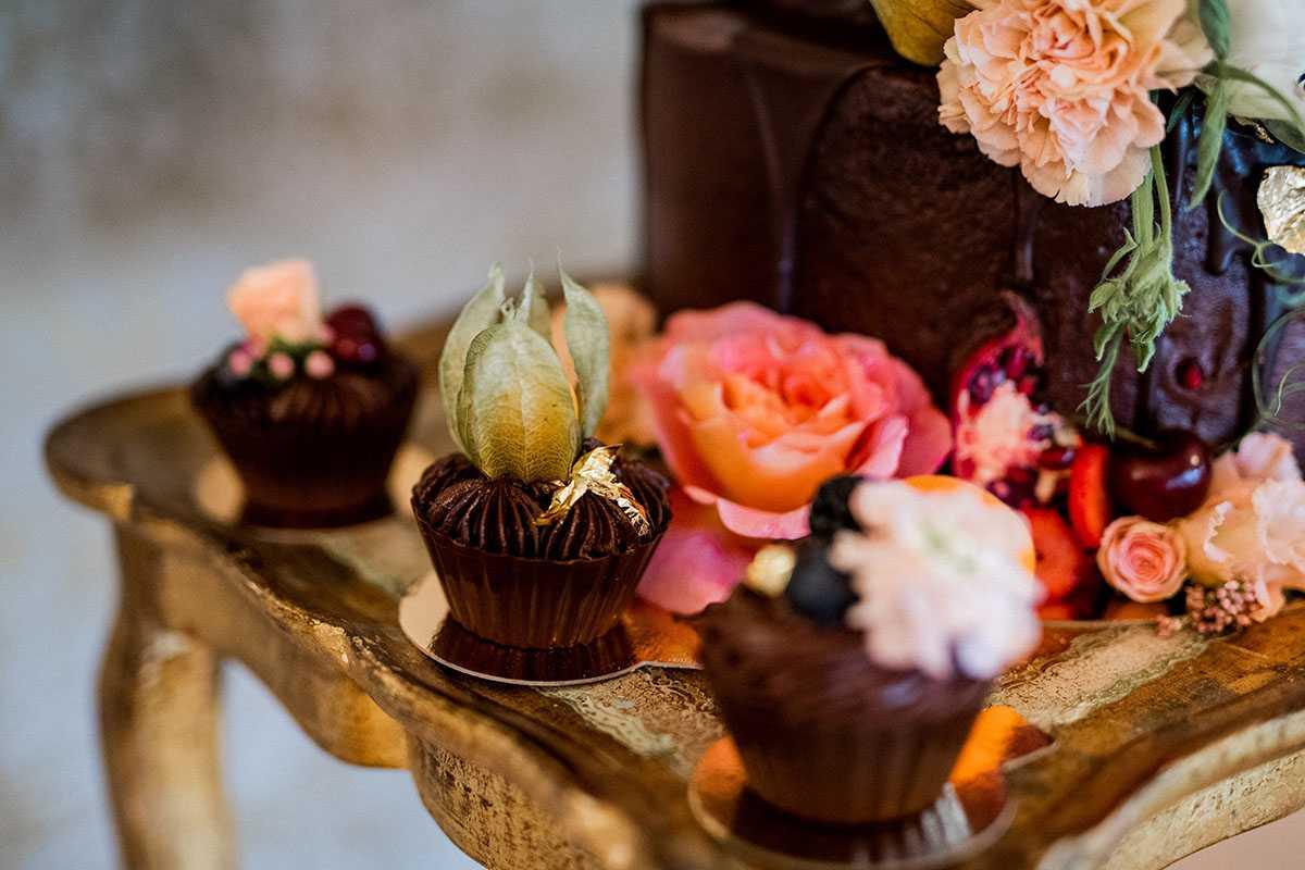 Schoko-Cupcakes mit Blumen und Fruechten
