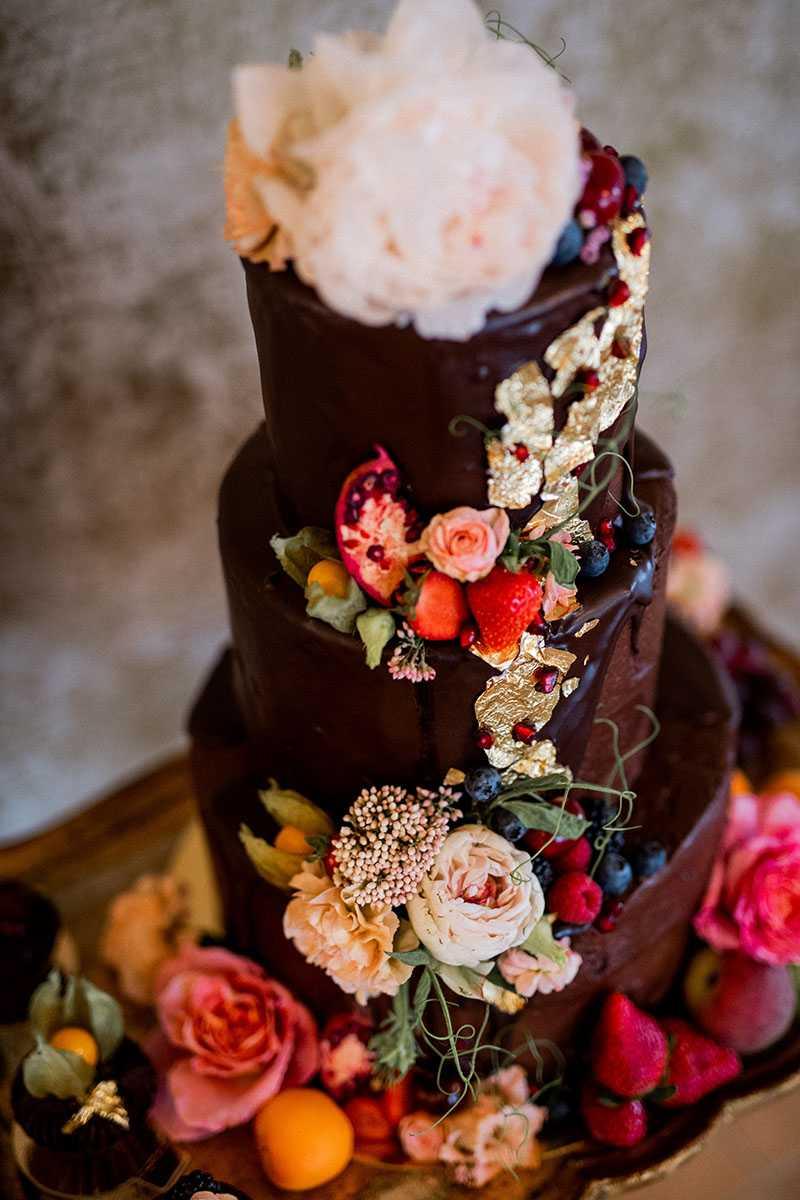 Mehrstoeckige Schoko-Hochzeitstorte mit Blattgold Blumen und Fruechten