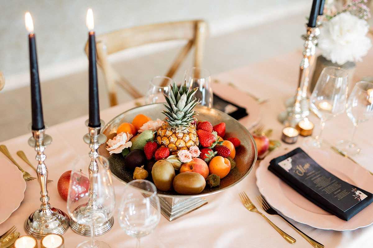Tischdekoration mit Kerzen und Obstschale