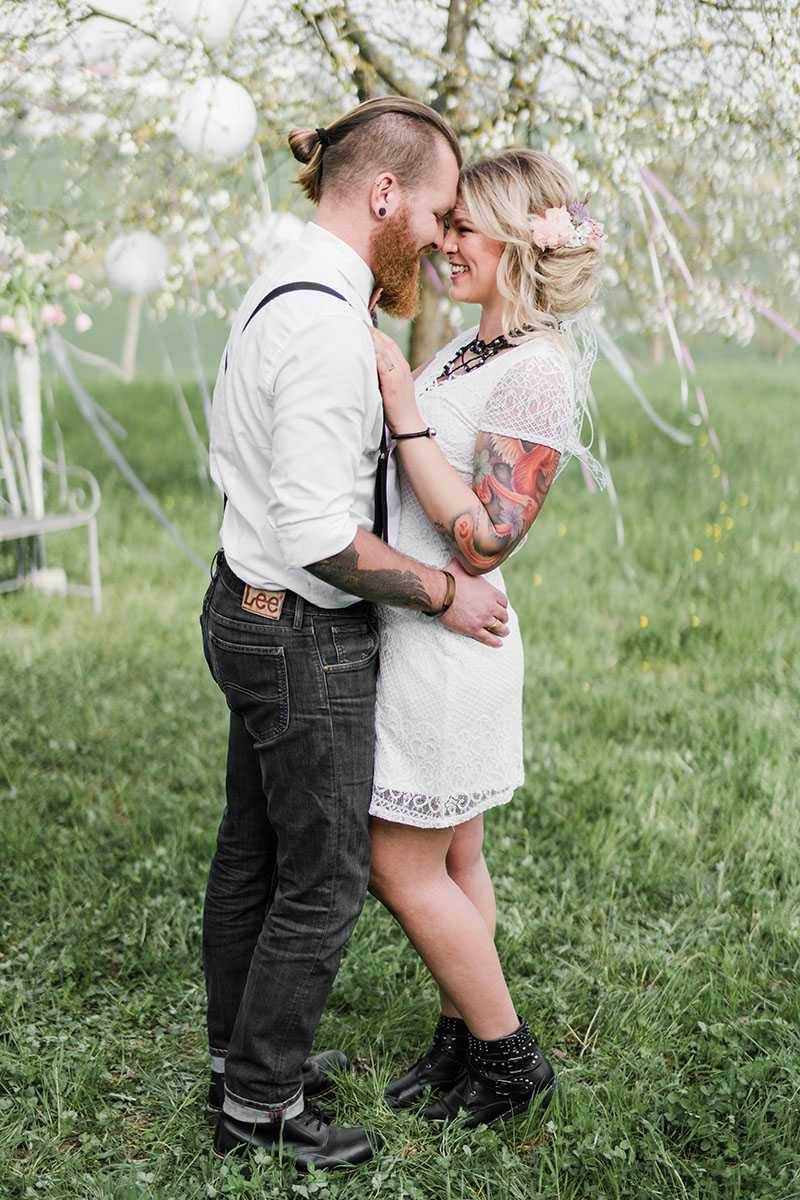 Brautpaar auf Wiese mit Baum im Hintergrund