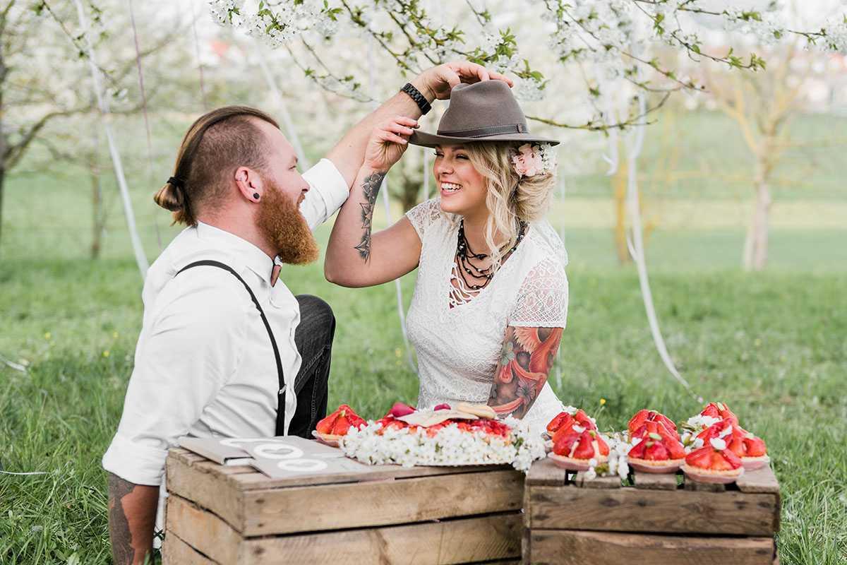 Brautpaar auf Wiese mit Erdbeertoertchen