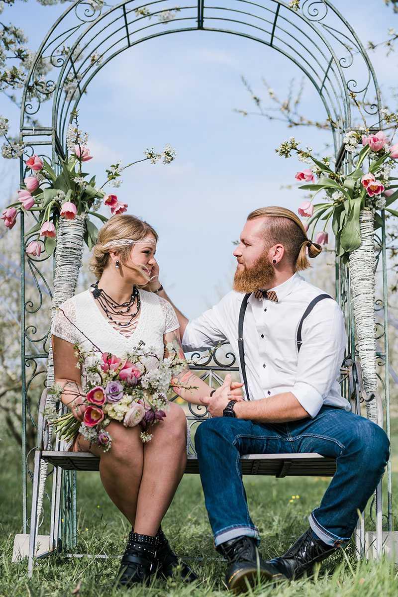 Brautpaar mit Blumenstrauss vor Traubogen