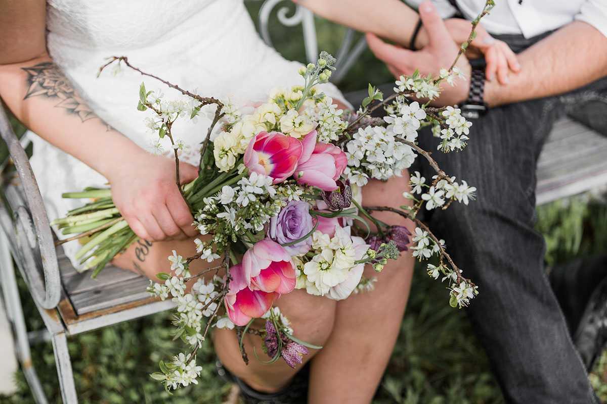 Brautpaar auf Bank mit Brautstrauss