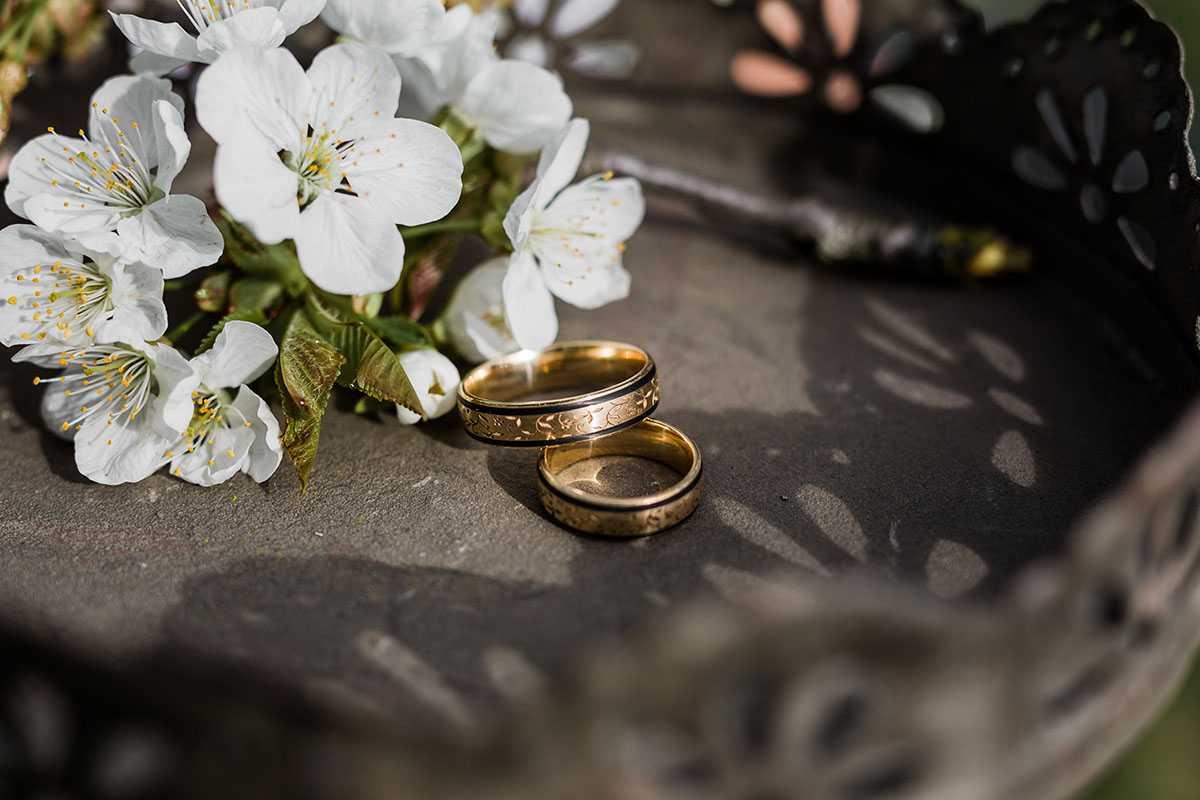 Goldene Eheringe auf Tablett mit Kirschblüten