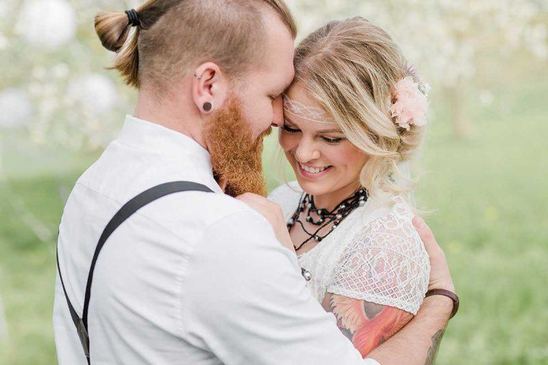 Braut und Braeutigam umarmen sich auf gruener Wiese
