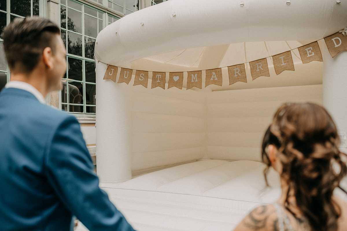Brautpaar mit weißer Hüpfburg