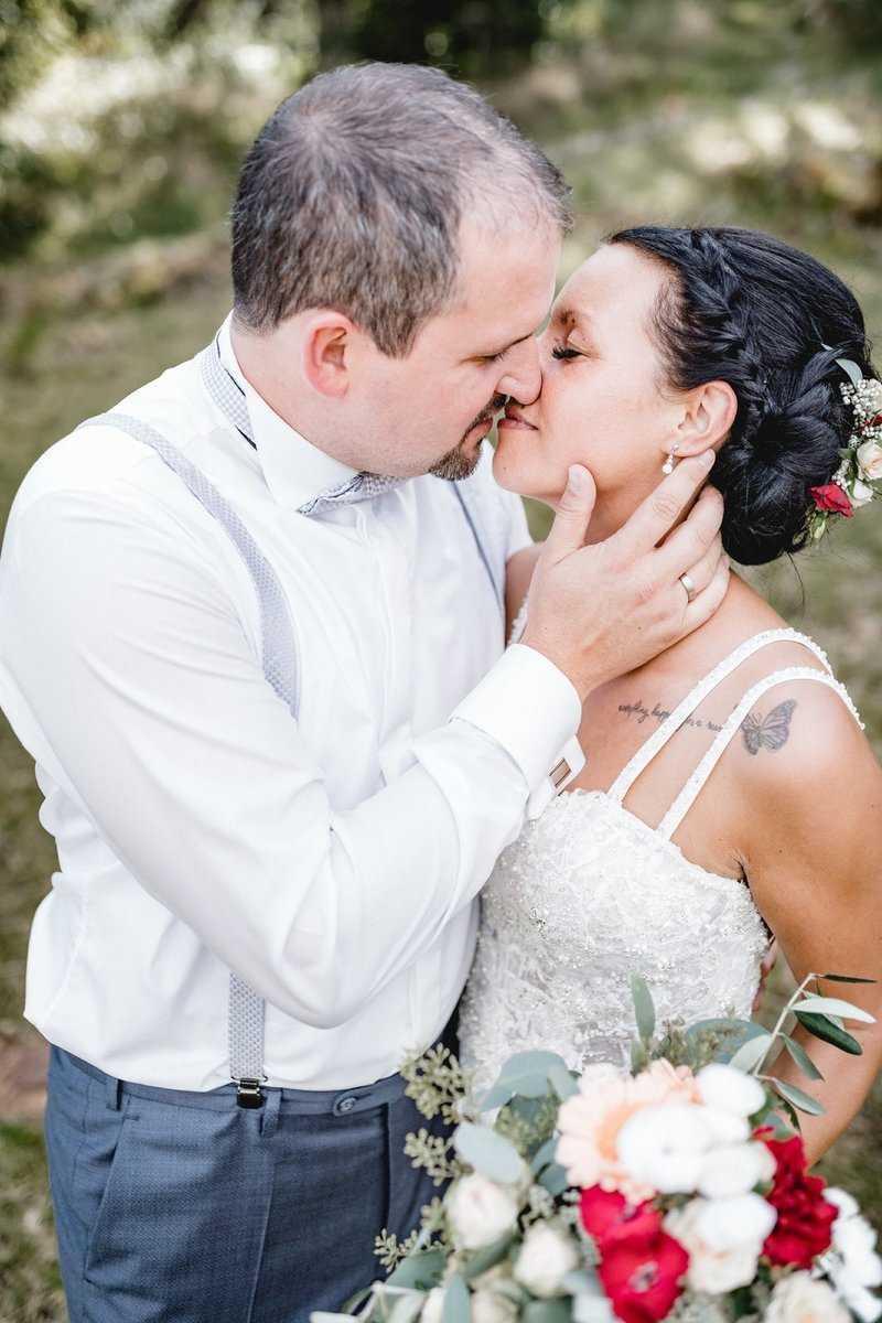 Küssendes Brautpaar mit Brautstrauß