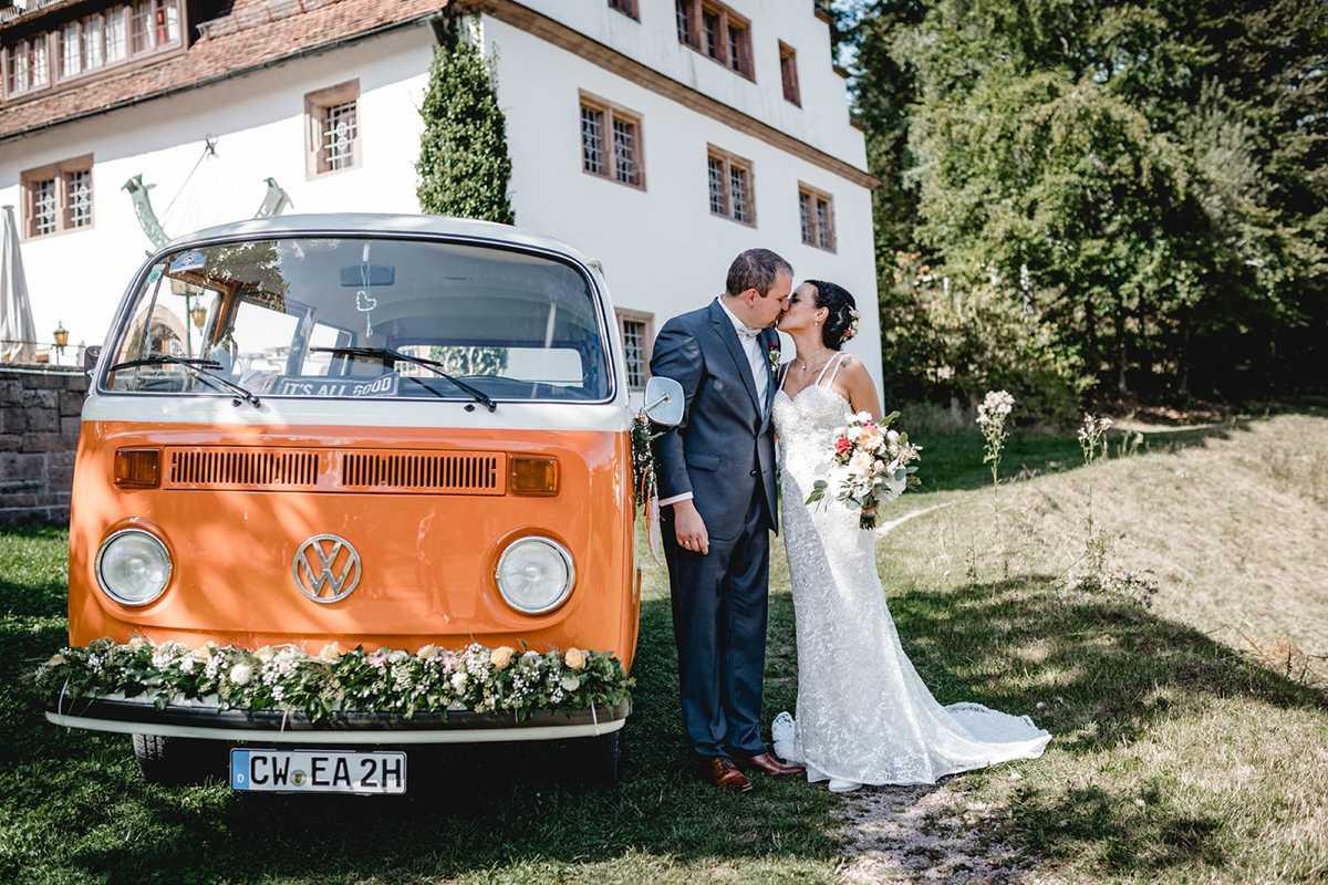 Küssendes Brautpaar mit VW-Bulli