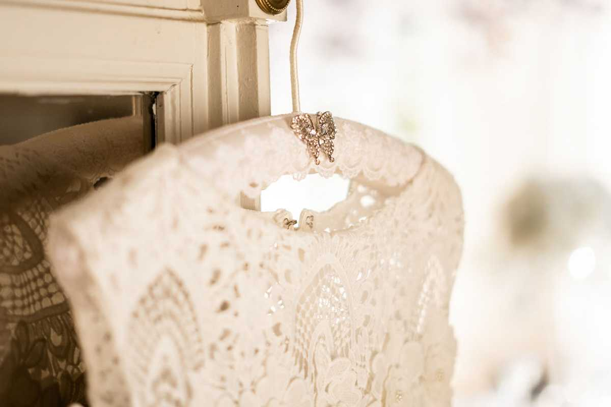 Brautkleid aus Spitze an einem Bügel mit Schmetterlings-Brosche