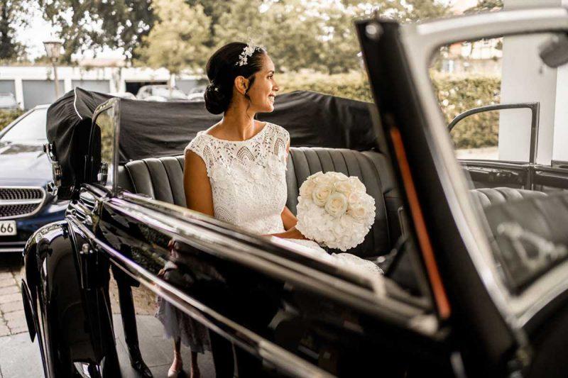 Braut mit Brautstrauß in einer schwarzen Limousine